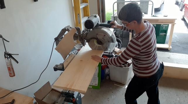 Brenda cutting rough cut pine boards to length